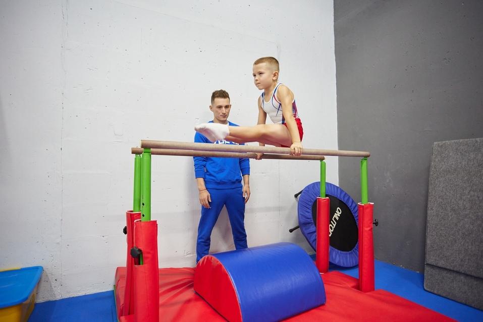 """Воспитанник """"Академии гимнастики"""" выполняет элемент на брусьях"""